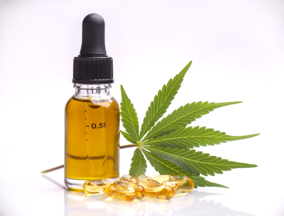 A marijuana leaf and CBD oil and capsules