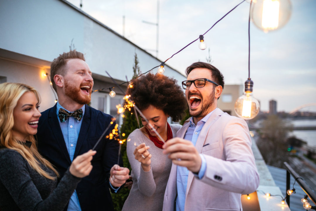 Multiracial and multi gender group of four friends at a rooftop party hold sparklers