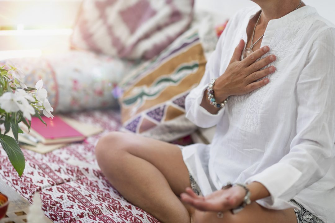 Woman tuning into her chakras to create a sacred space.