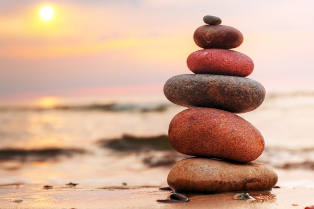 balancing rocks on beach at sunset
