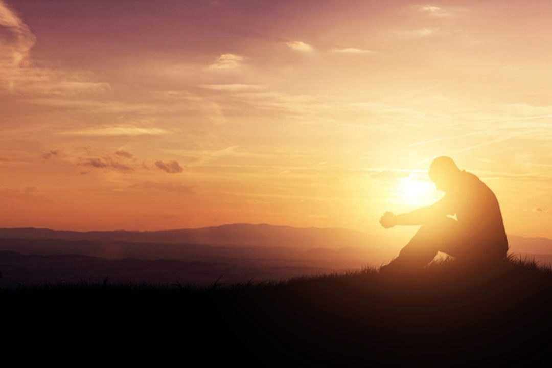 Man on hill at sunset