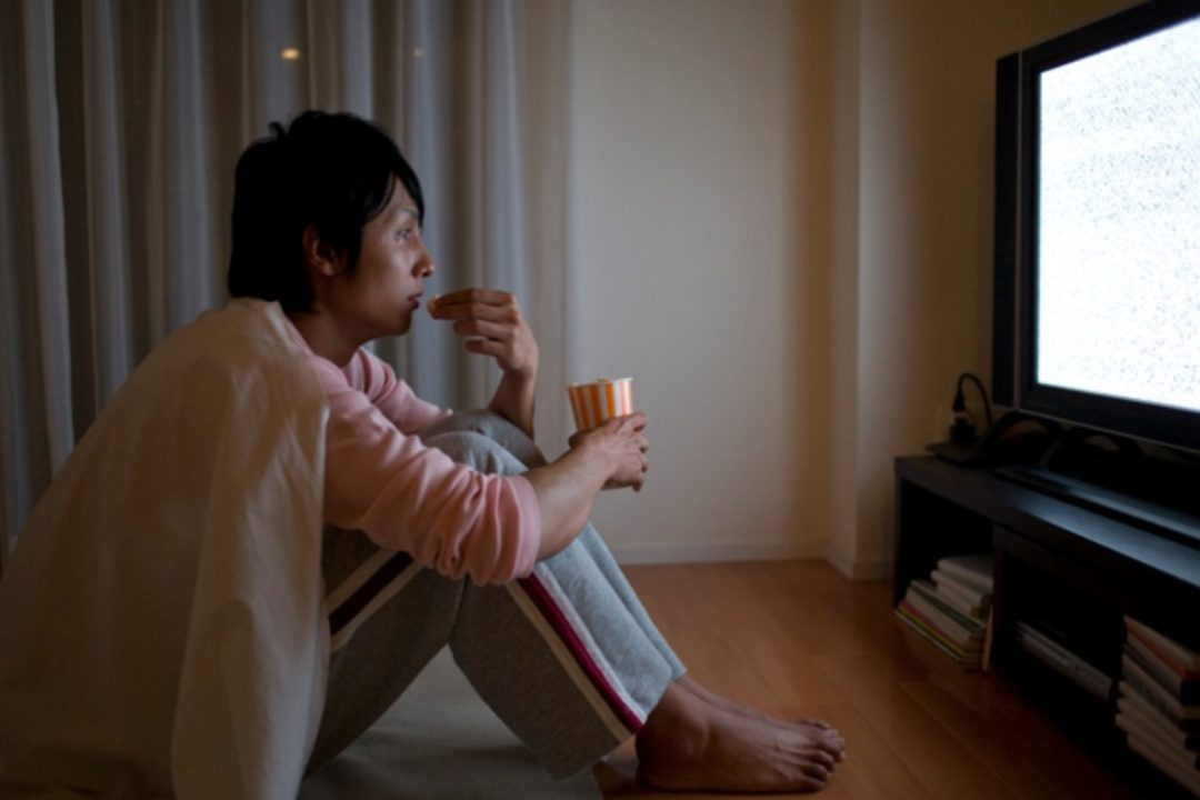 Adult sits with snack watching television