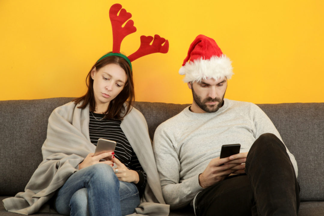 Couple wearing a santa hat and reindeer antlers sit on the couch staring at their phones