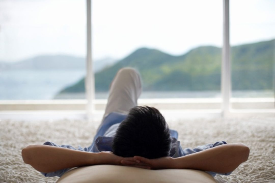 Man lying down looking out window