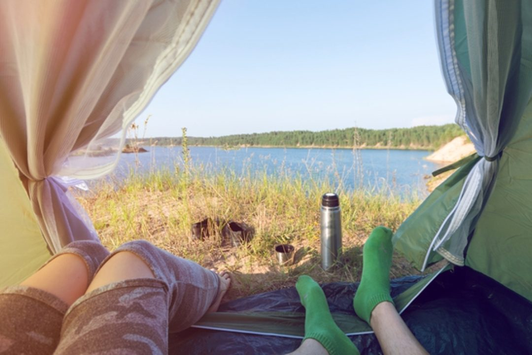 Couple looks at lake from inside tent