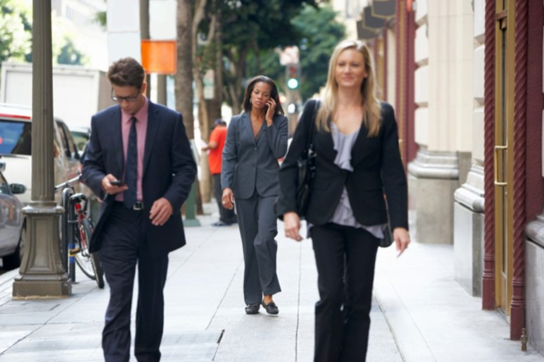 Business people walking while using their phones