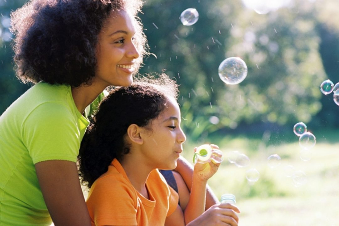 Woman blowing bubbles with daughter