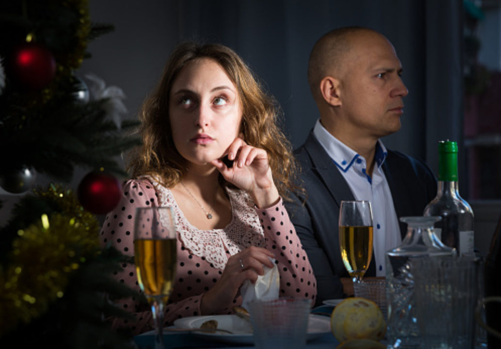 Woman sitting next to man at dinner table with head turned, rolling her eyes
