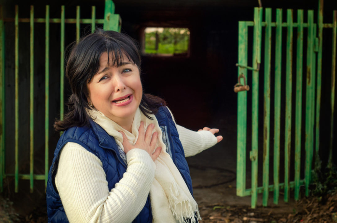A middle-aged woman looking afraid with hand over heart stands in front of the open gates to a tunnel