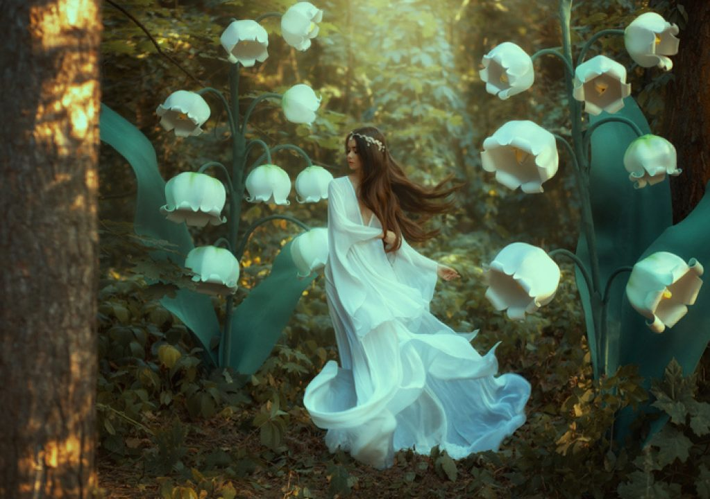 A female elf walks among the flowers in the garden.