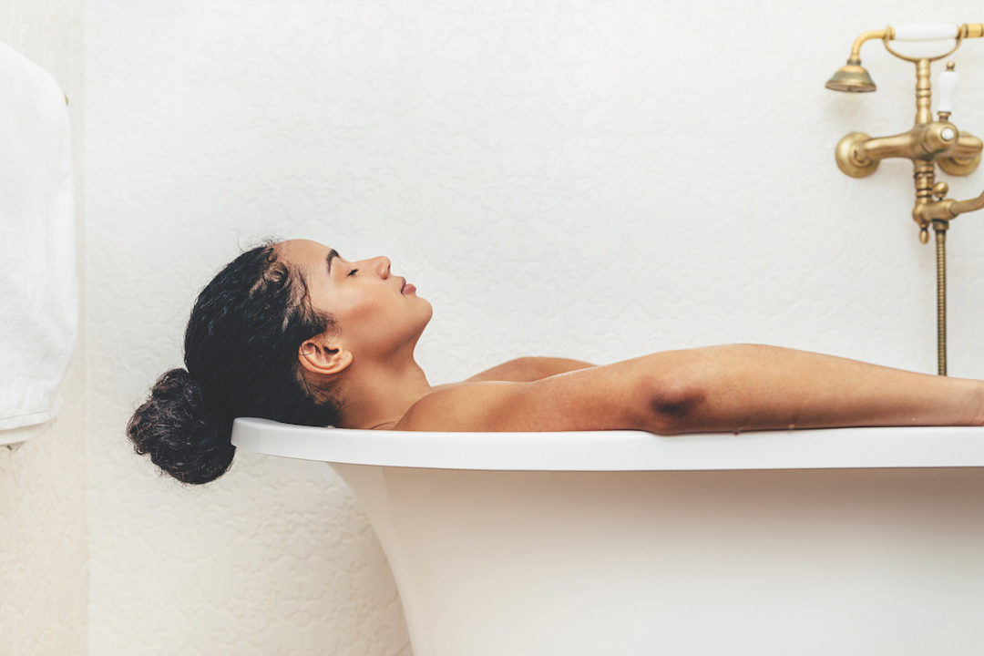Side view of young woman having a bath