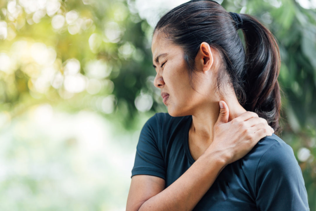 A young woman massages her tight neck.