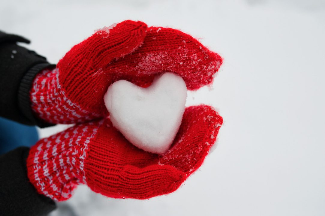 Gloved hands offering a gift of a heart made out of snow.
