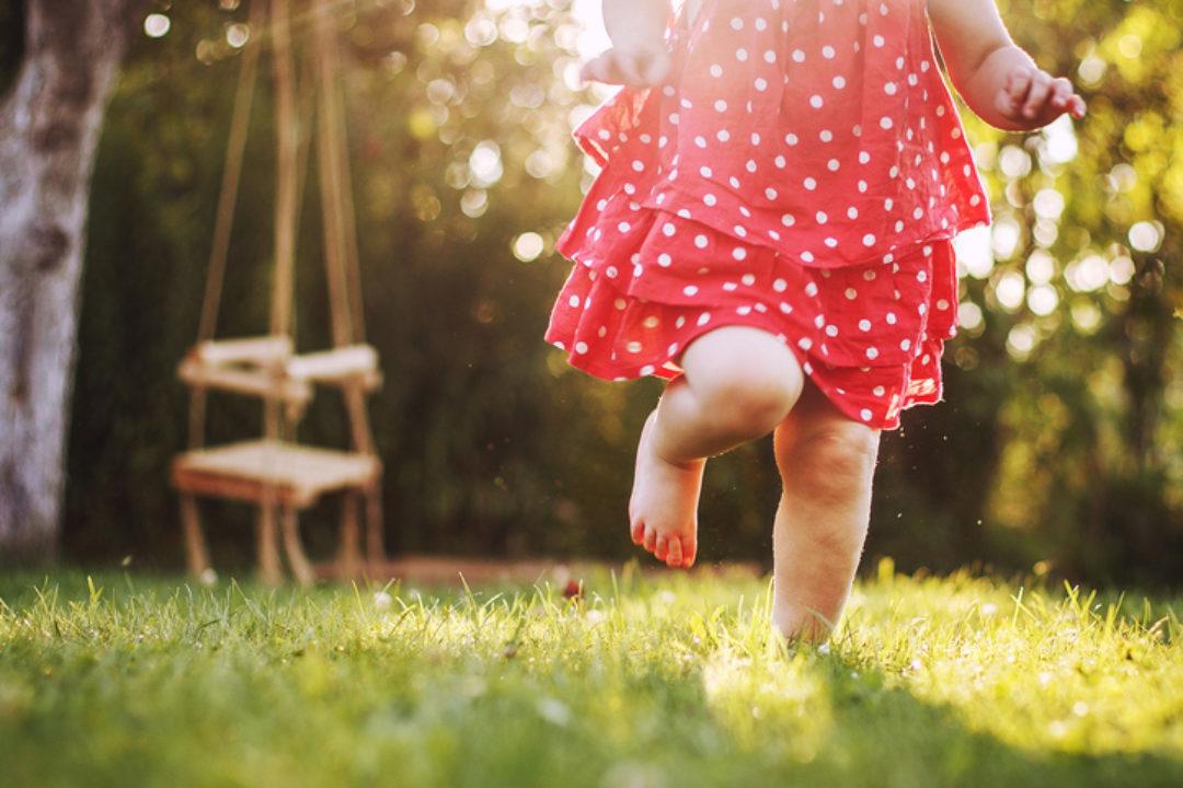 A barefoot girl runs through the grass