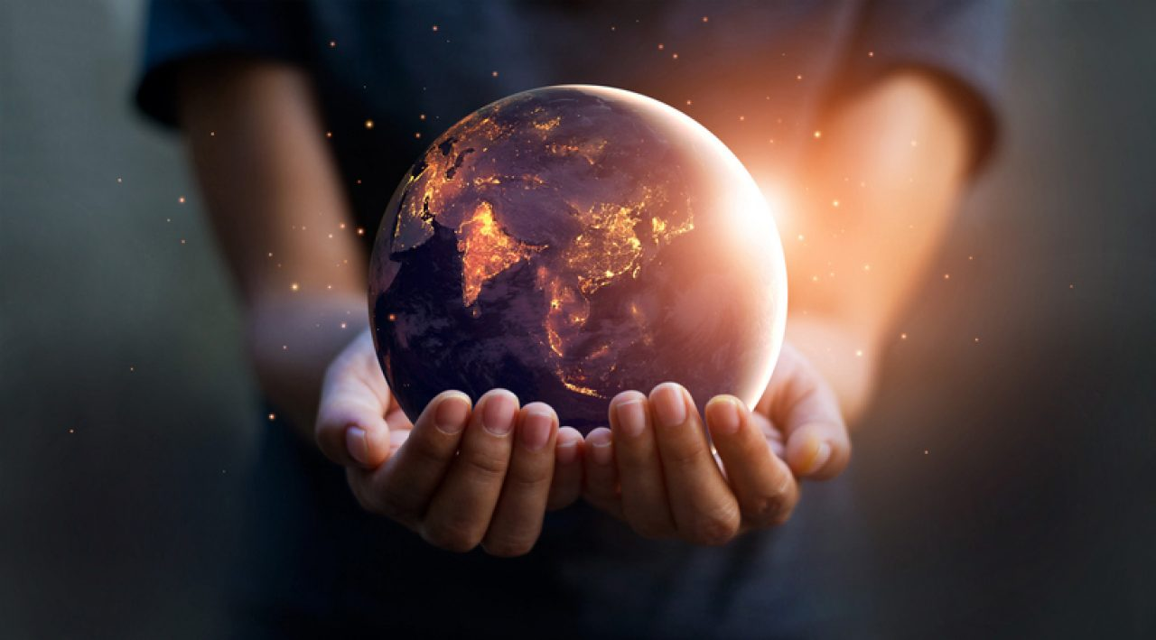 Person holding a model of the earth lit from within