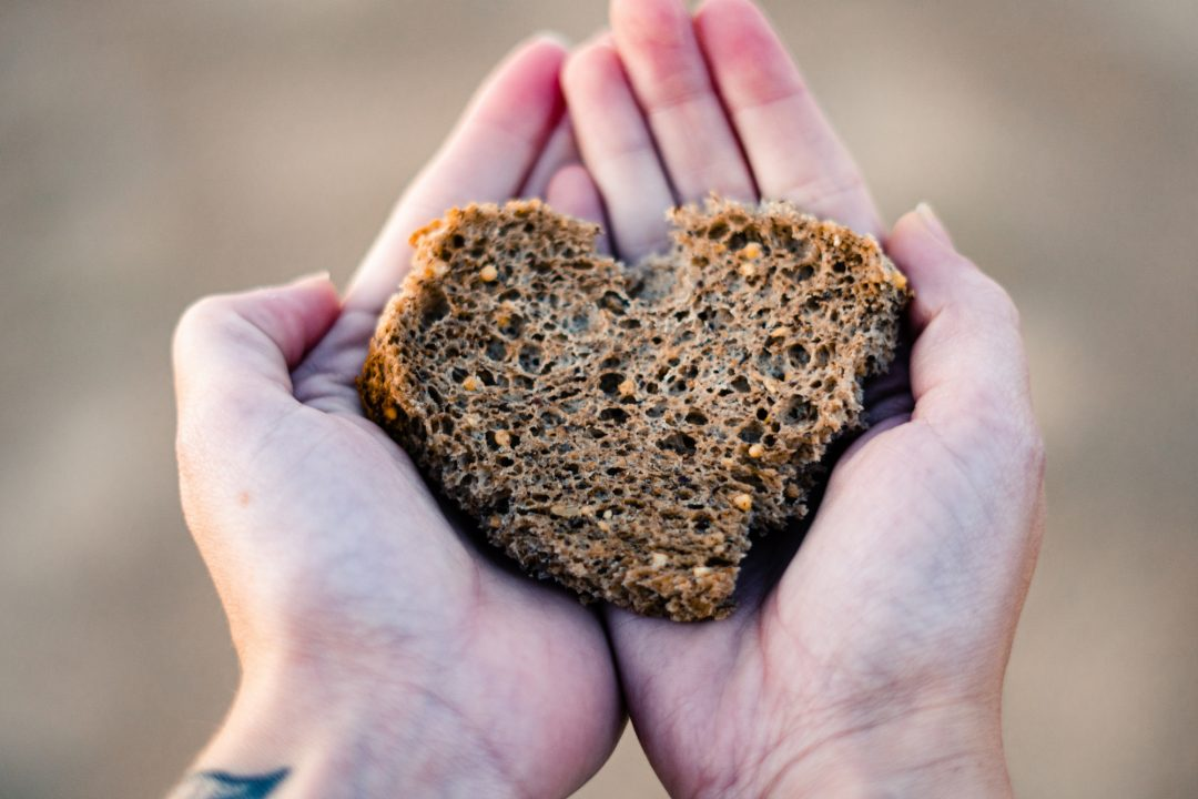 Pair of hands holding a slice of Gluten Free Happy Campers bread
