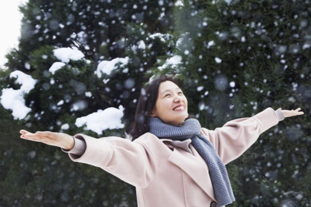 Happy woman with arms outstretched in snow