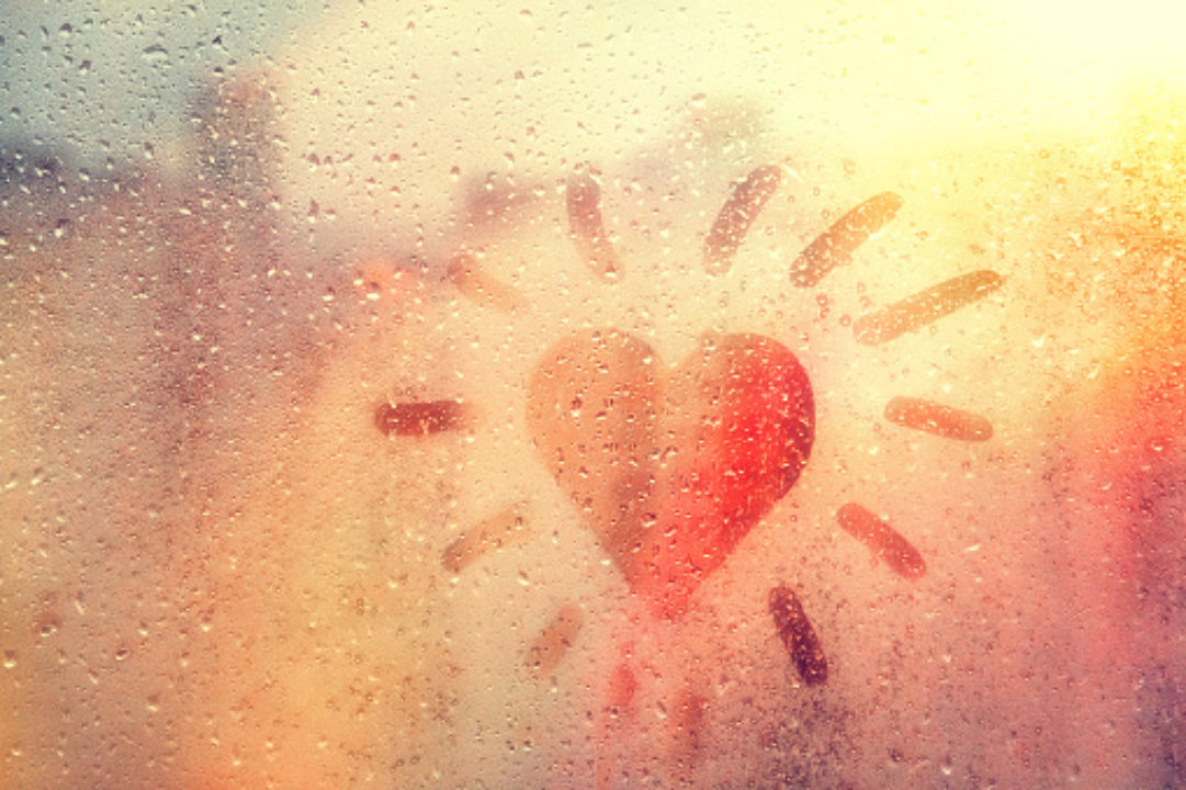Hand-drawn orange, heart-shaped like sun on rainy window
