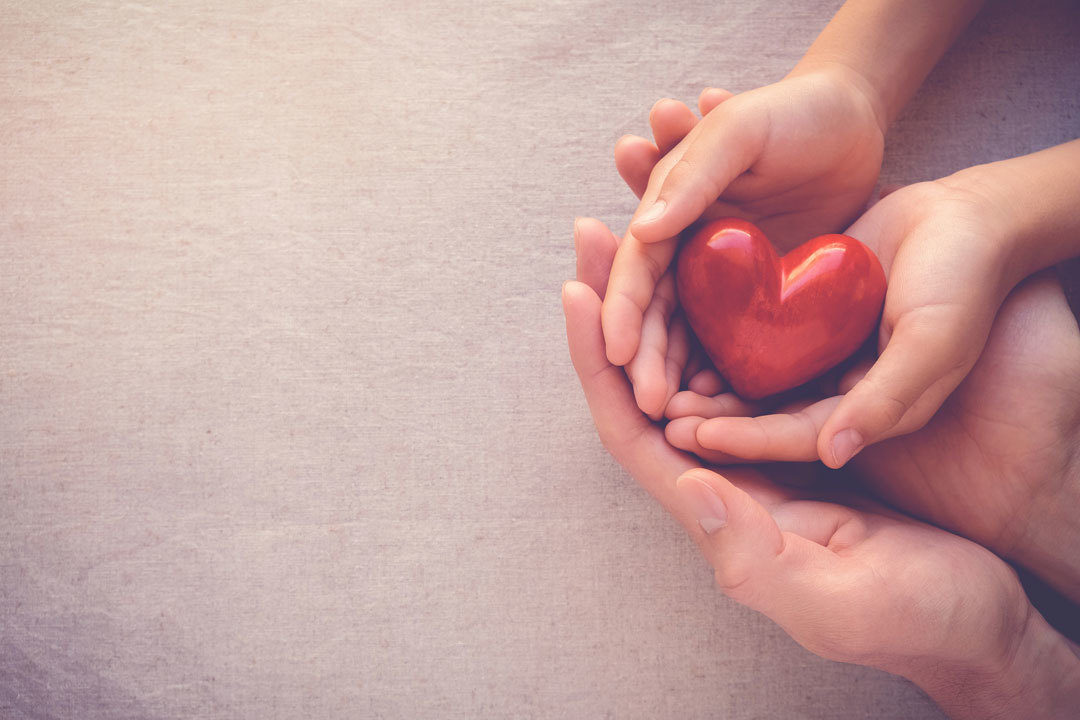 Adult and child hands holding heart