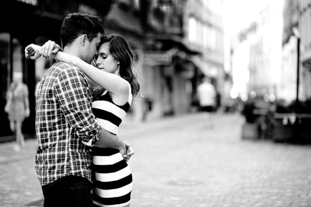Young couple embracing on street