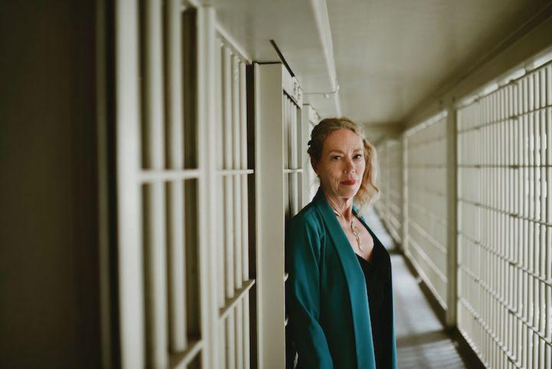 Dr. Karen Gedney standing in front of prison bars