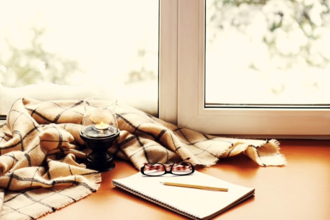 Notepad and candle in window