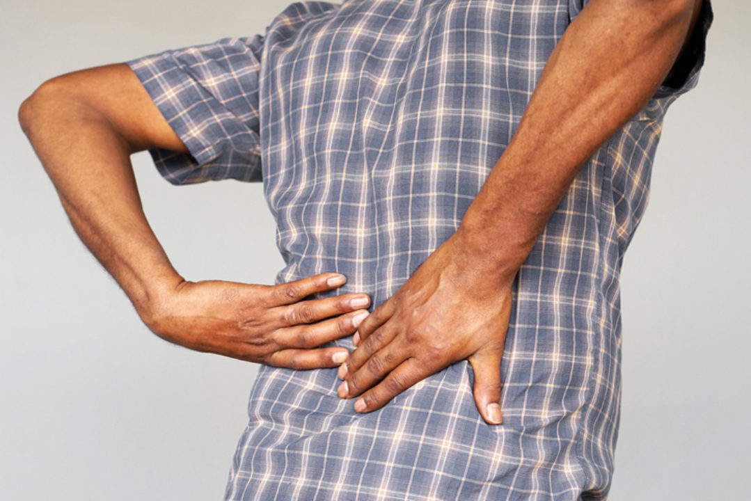 A man grabs his painful back