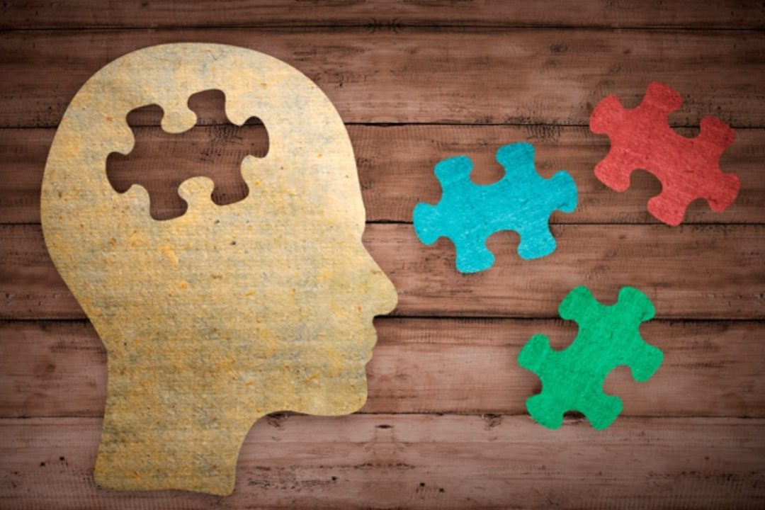 Head and puzzle pieces on wood surface