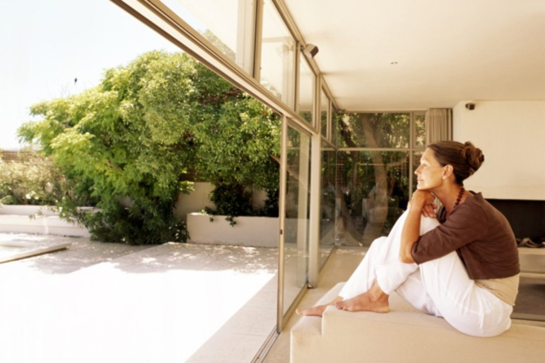 Woman looking out large windows in modern home