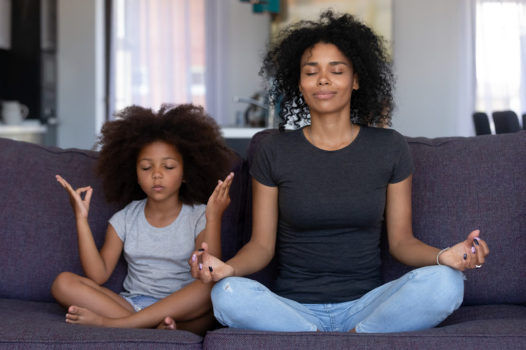 Black mom and daughter finding zen doing yoga on the couch