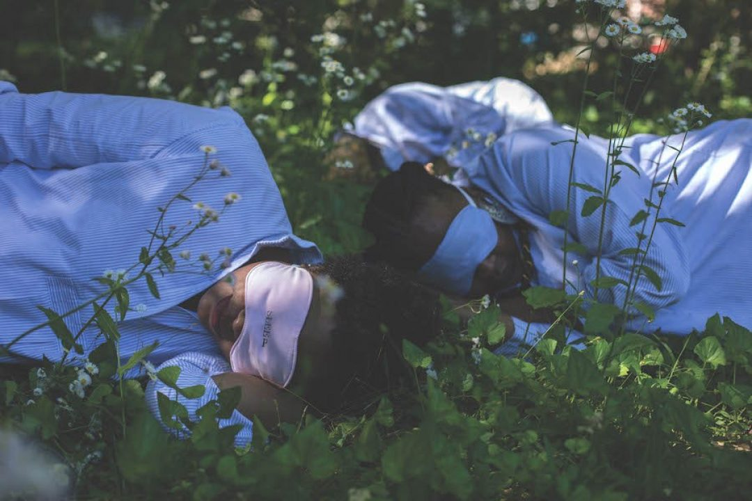 two women in sleep masks laying in the foliage