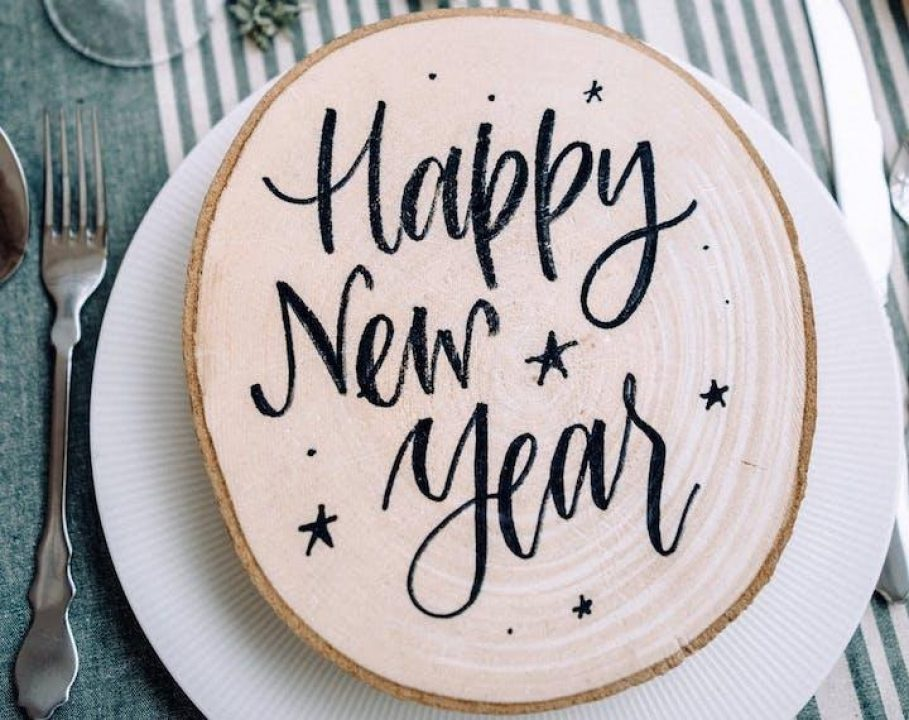 Happy New Year written on wooden place mat at table