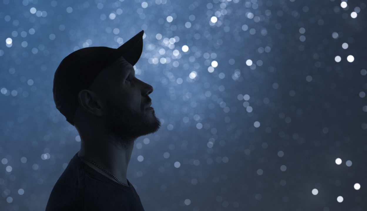 A man looks up at a starry sky and contemplates God and how to listen to God.
