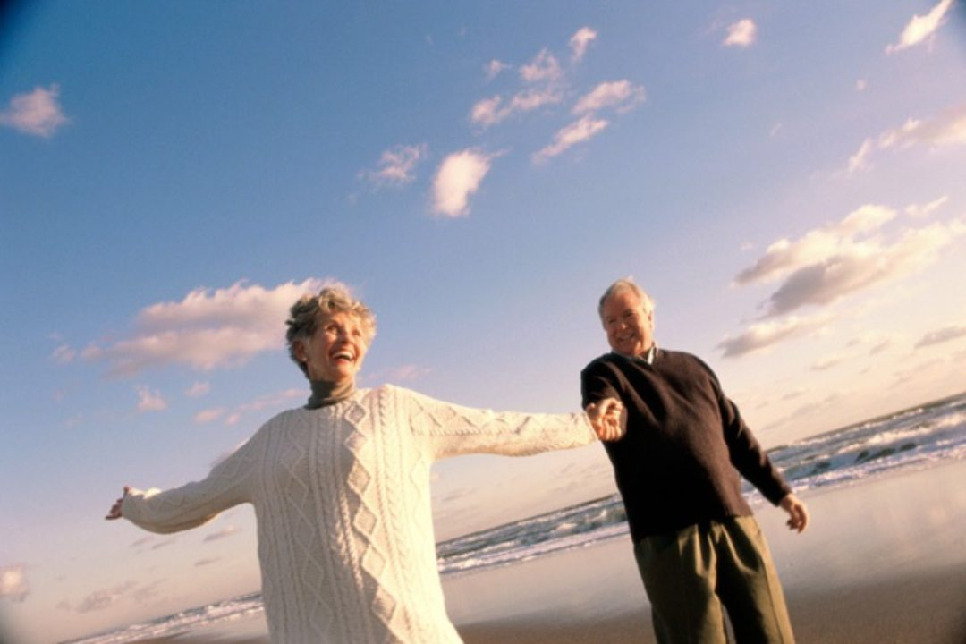 Older couple holding hands on beach