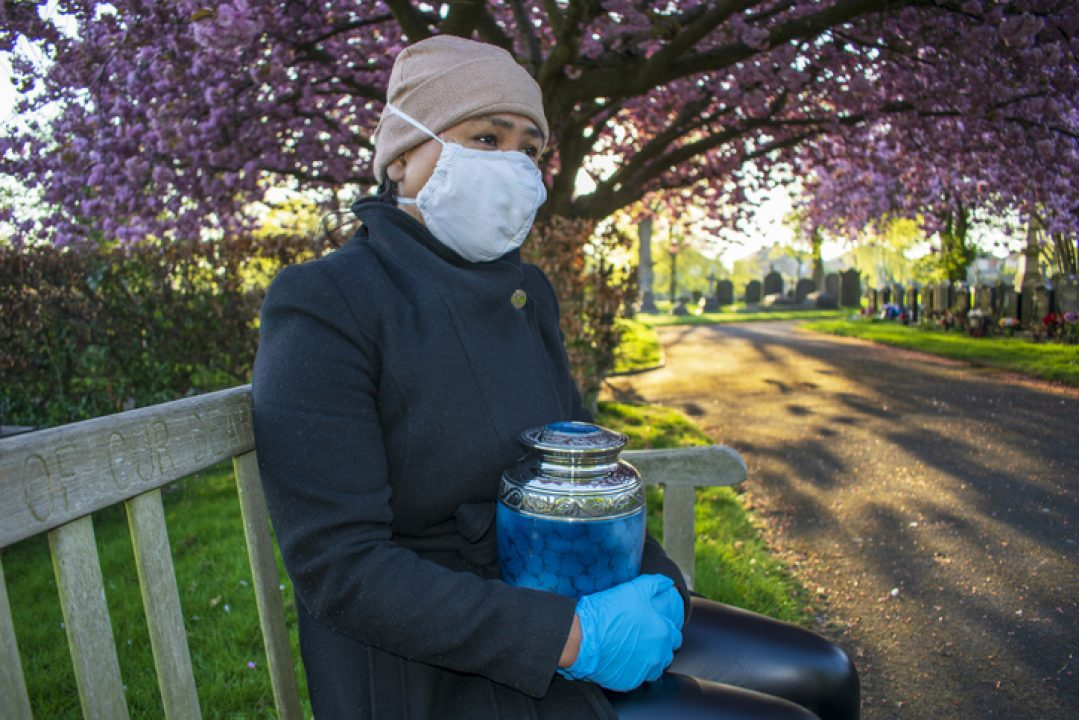 Person in mask and gloves holding funeral urn during COVID-19