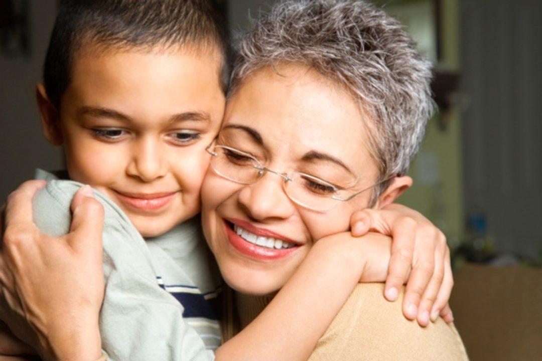 Grandma hugging grandson and smiling