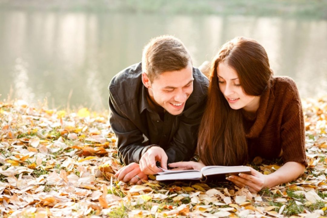 Couple reading a journal together