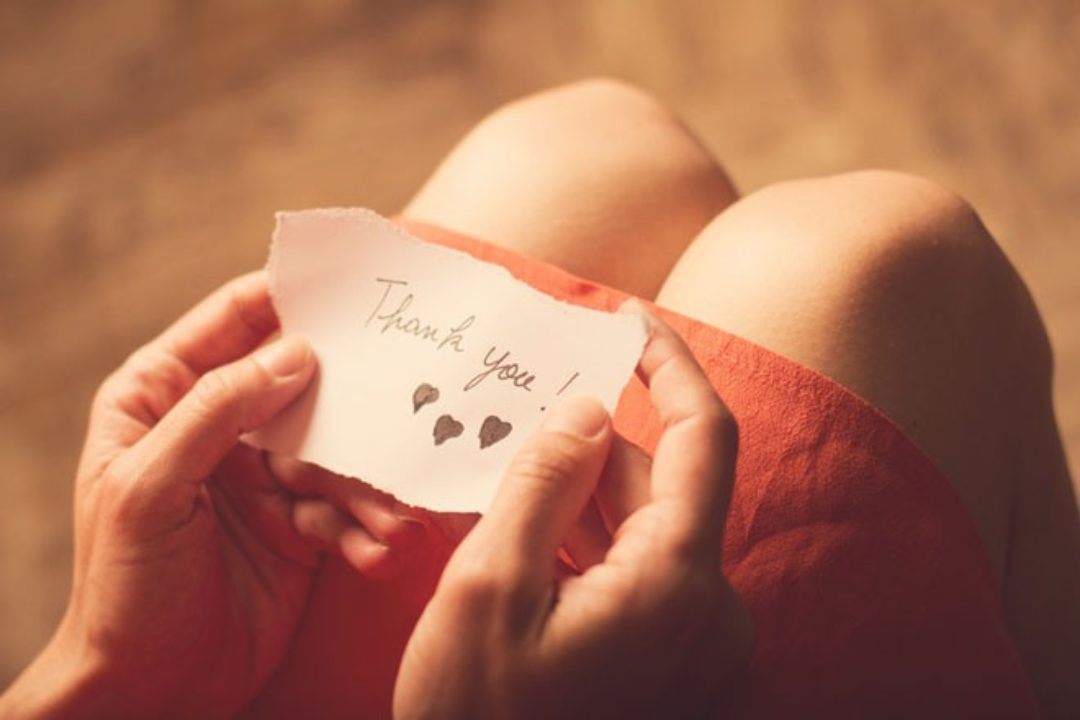 Woman holding gratitude note