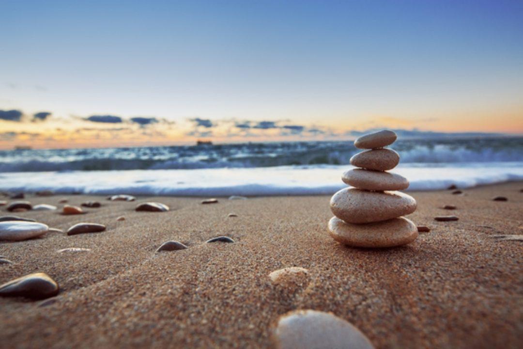 Balancing stones on beach at sunrise