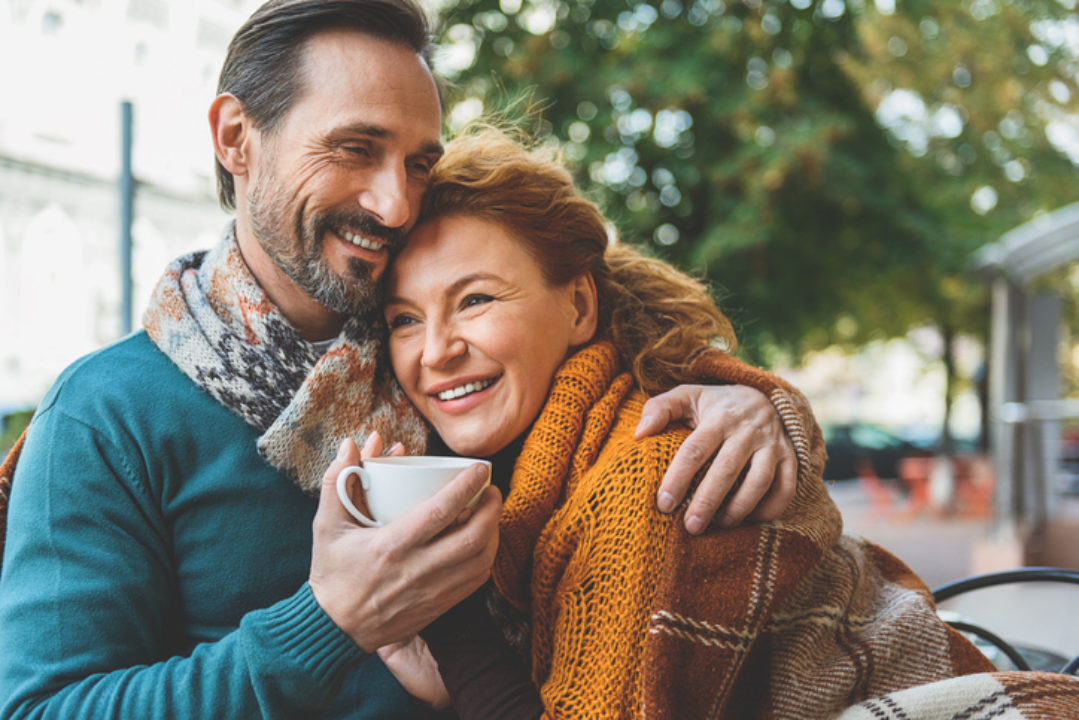 Smiling couple hugging.