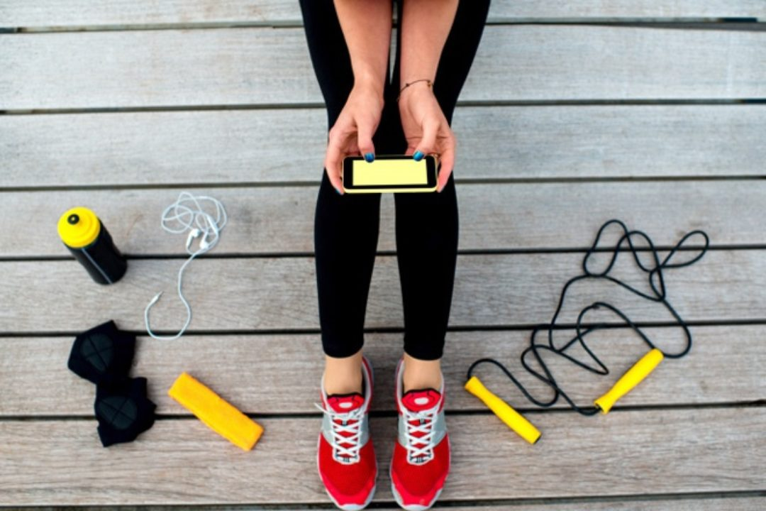 Woman with smartphone and exercise equipment on deck