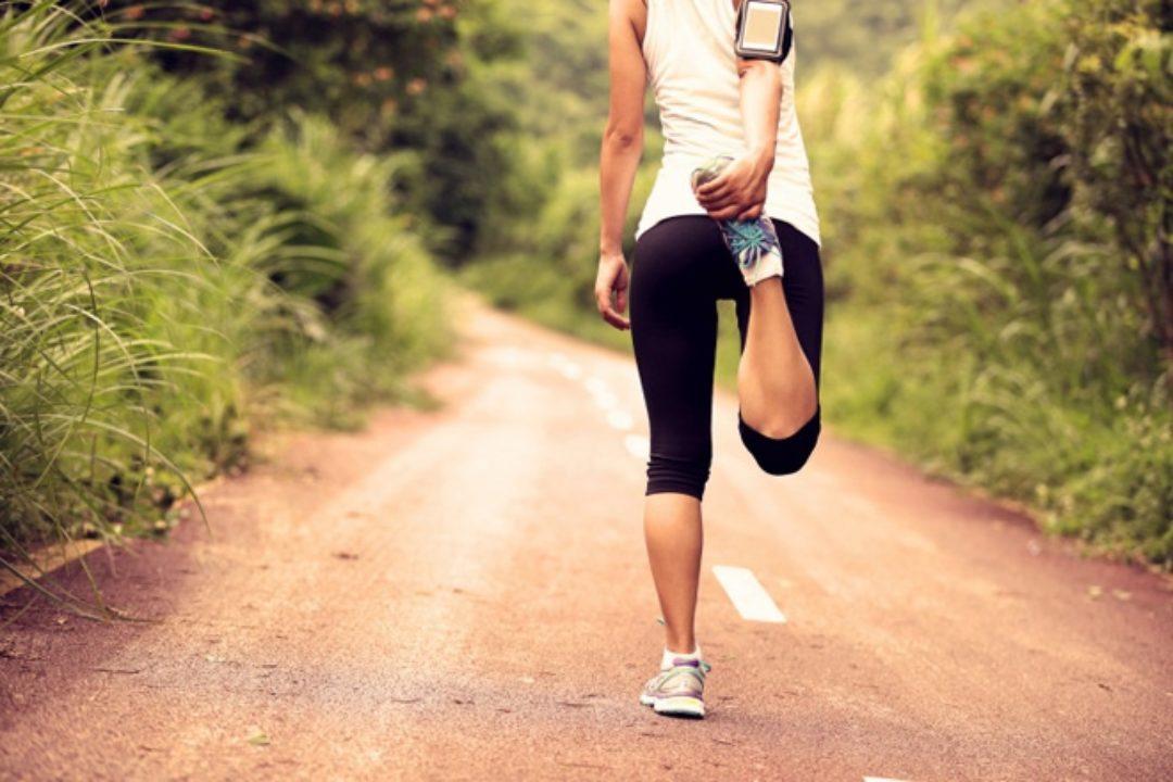 Woman stretching leg on dirt road