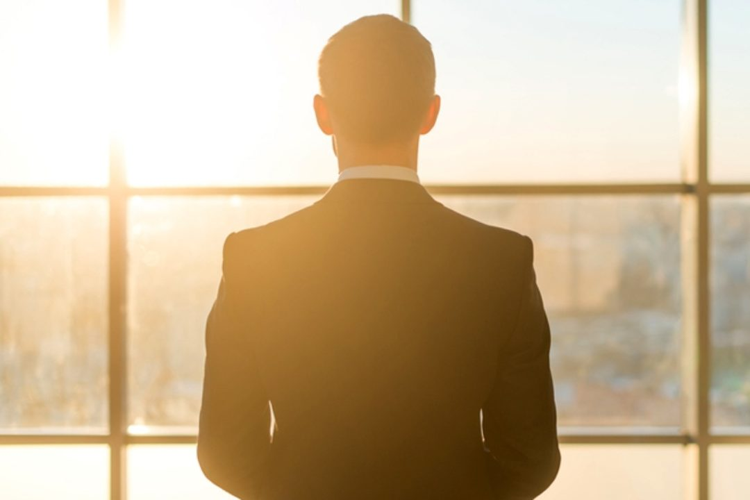 Man in suit looking out window