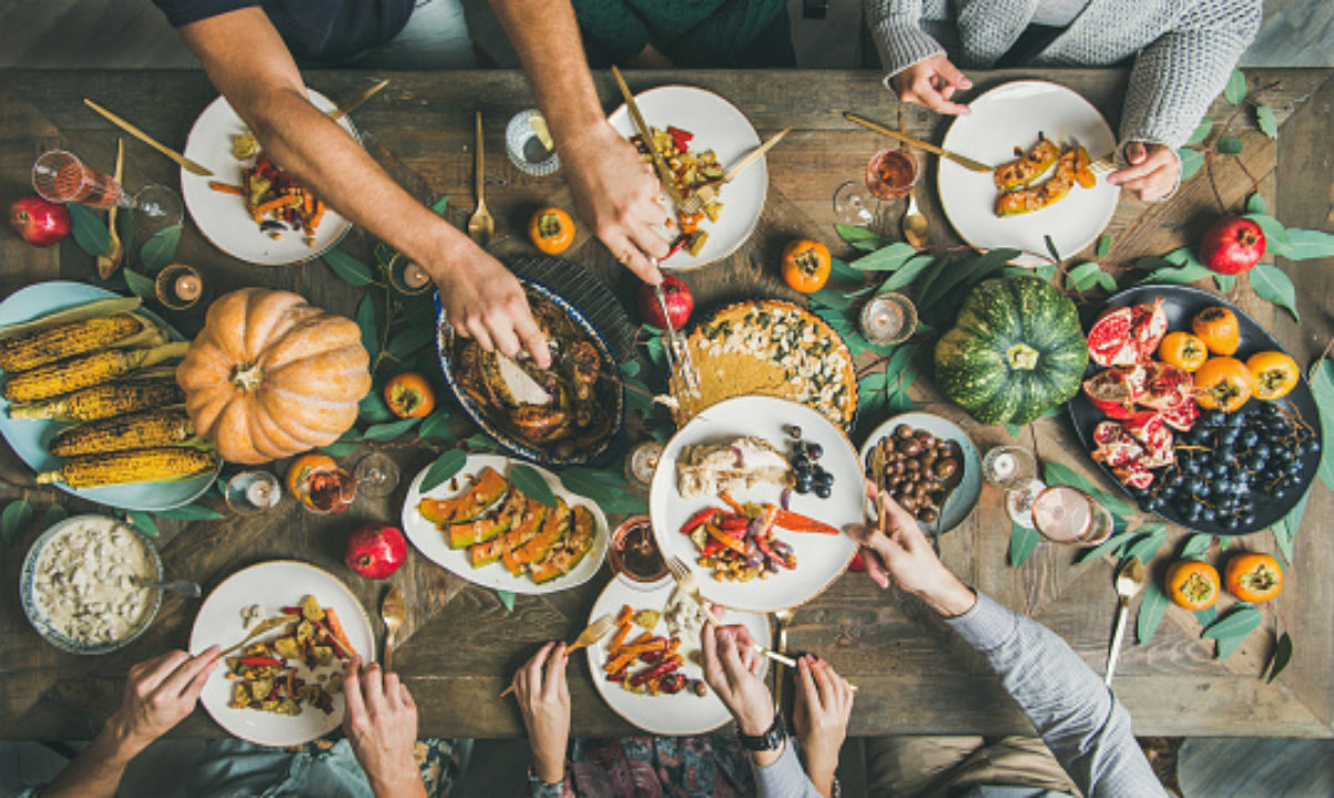 Top view of festive Thanksgiving Day table with turkey, pumpkin pie, roasted seasonal vegetables and fruit
