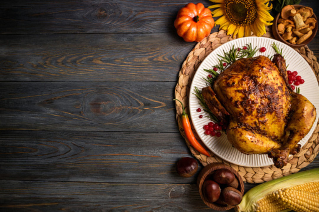 Roast turkey with autumn vegetables for thanksgiving dinner on wooden background