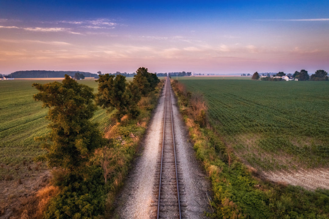 The railroad track going between the crops of corn and soybeans on a summer morning in Ohio.
