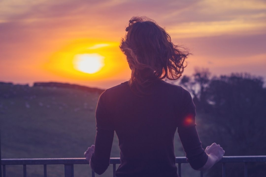 Woman at sunset looking toward sky