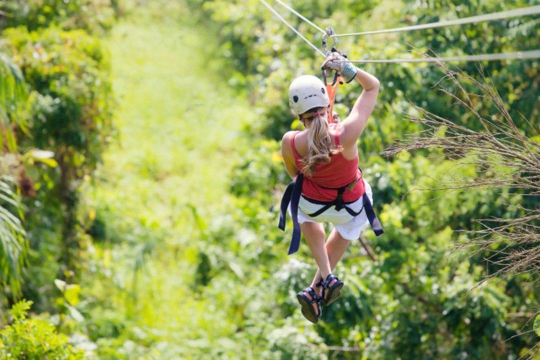 Woman ziplining in bright jungle