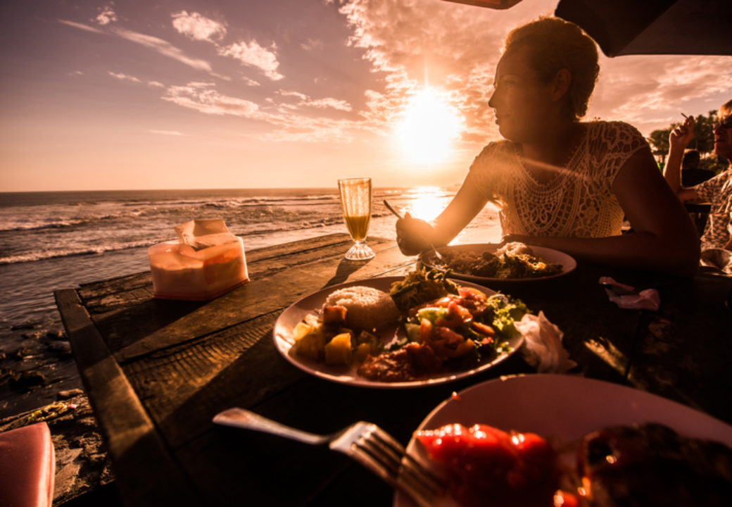 Woman eating dinner in restaurant on the tropical beach at sunset.