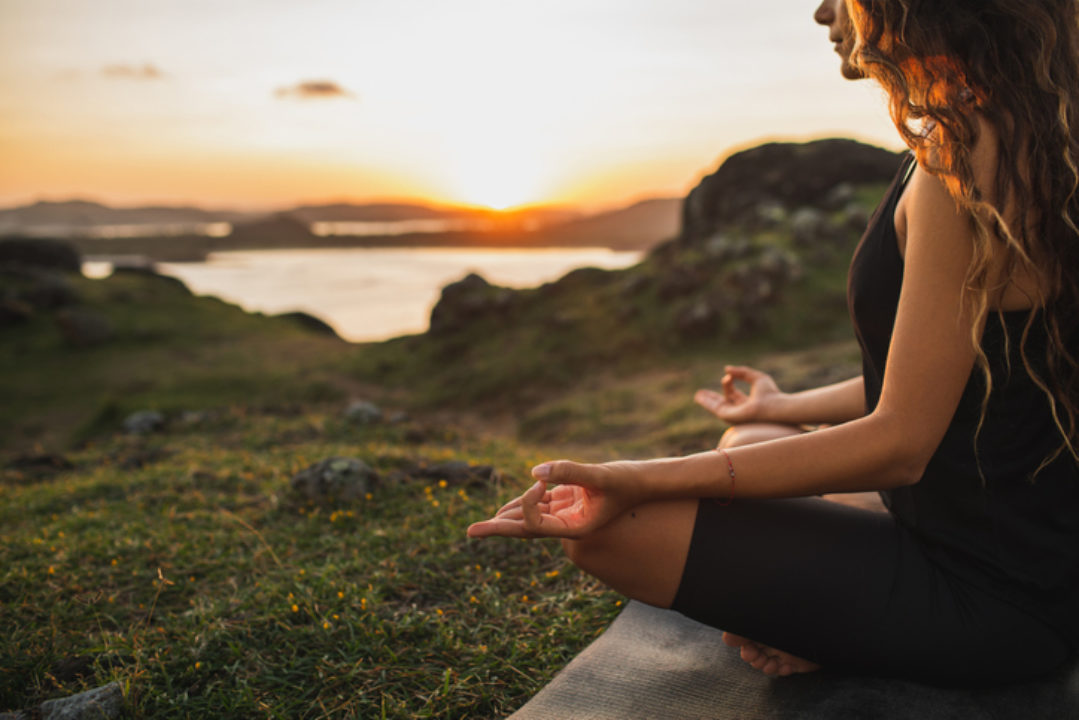 Woman doing yoga outdoors at sunrise in lotus position